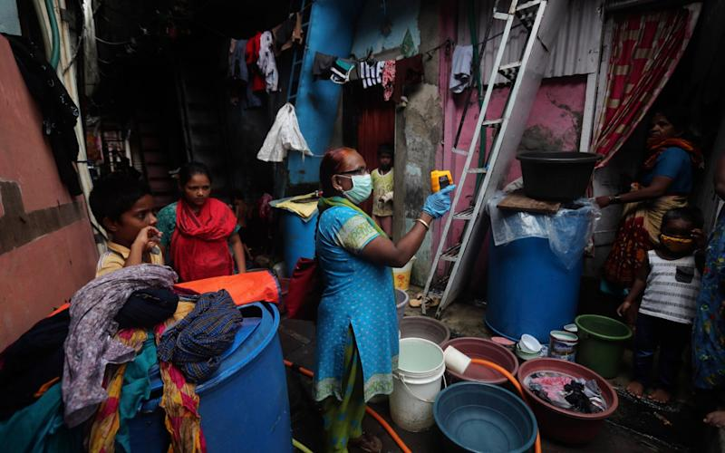 A health worker screens people for Covid-19 at Dharavi, one of Asia's biggest slums, in Mumbai, India, which now has the world's third-highest case tally - AP