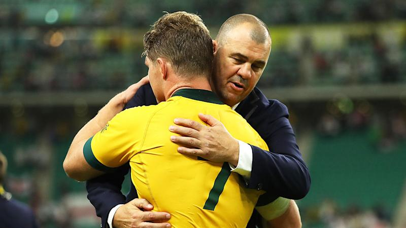 Wallabies captain Michael Hooper and coach Michael Cheika embrace after the loss to England.