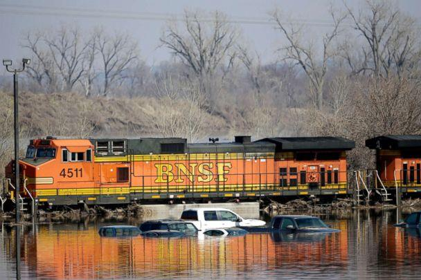 PHOTO: Cars sit in flood waters from the Platte River alongside a BNSF train, in Plattsmouth, Neb., March 17, 2019. [Nati Harnik/AP)