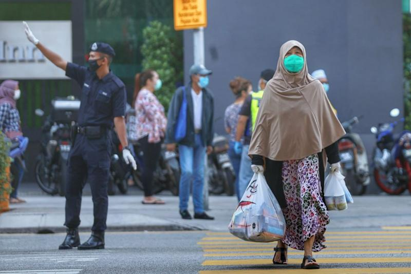 A woman makes her way out of the Chow Kit wet market with her groceries in Kuala Lumpur March 27, 2020. ― Picture by Ahmad Zamzahuri