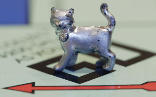 The newest Monopoly token, a cat, rests on the game board at Hasbro Inc. headquarters, in Pawtucket, R.I., Tuesday, Feb. 5, 2013. Voting on Facebook determined that the cat would replace the iron token. (AP Photo/Steven Senne)