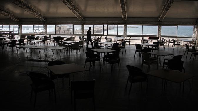Pekerja Palestina terlihat di dalam kafe yang kosong Gaza City, 17 September 2020. Lebih dari 500 tempat wisata di Gaza, termasuk hotel, restoran, gedung pernikahan, dan kafe, telah ditutup menyusul penerapan lockdown yang menyebabkan 7.000 pekerja menganggur sementara. (Xinhua/Rizek Abdeljawad)