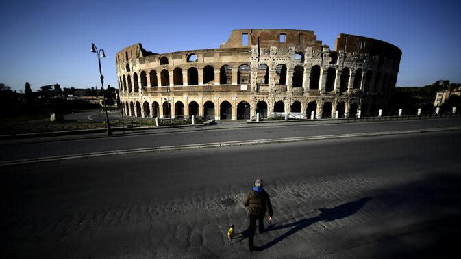 Seorang pria membawa anjingnya jalan-jalan di depan Colosseum, Roma, Italia, 3 April 2020. Menurut Departemen Perlindungan Sipil Italia pada 6 April 2020, jumlah kasus virus corona COVID-19 di negara tersebut menjadi 132.547 infeksi, 16.523 meninggal, dan 22.837 sembuh. (Filippo MONTEFORTE/AFP)