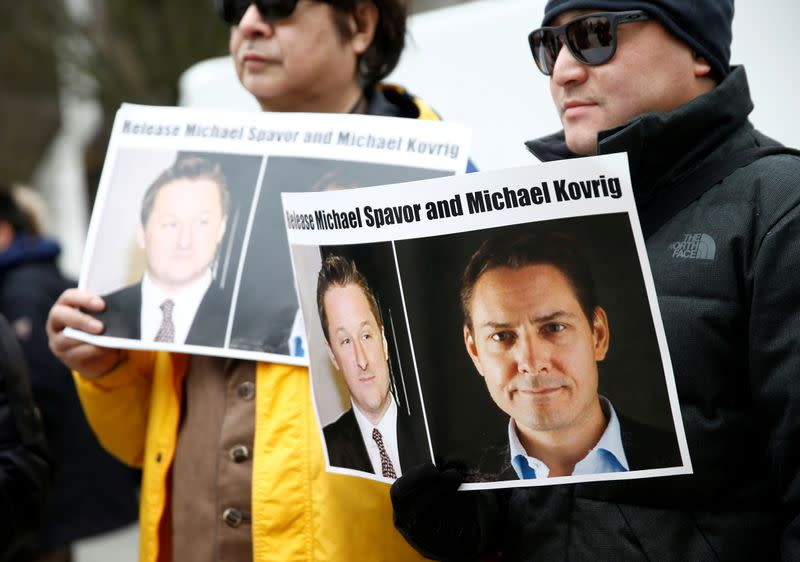 People hold signs calling for China to release Canadian detainees Spavor and Kovrig during an extradition hearing for Huawei Technologies Chief Financial Officer Meng Wanzhou at the B.C. Supreme Court in Vancouver