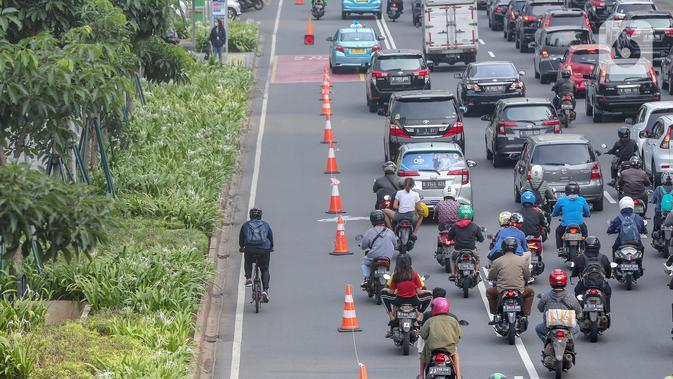 Warga bersepeda setelah jam kerja di jalur khusus sepeda kawasan Jalan Sudirman, Jakarta, Selasa (14/7/2020). Jam operasional dari Senin sampai Jumat pagi harinya jam 06.00 – 08.00 WIB, kemudian untuk sore dari jam 16.00 – 18.00 WIB. (Liputan6.com/Fery Pradolo)