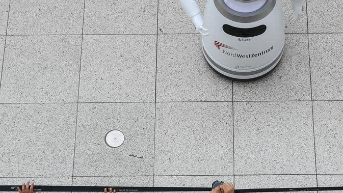 Anak-anak mengamati sebuah robot pintar yang menjelaskan tentang langkah pencegahan COVID-19 di sebuah pusat perbelanjaan di Frankfurt, Jerman, pada 12 September 2020. (Xinhua/Lu Yang)