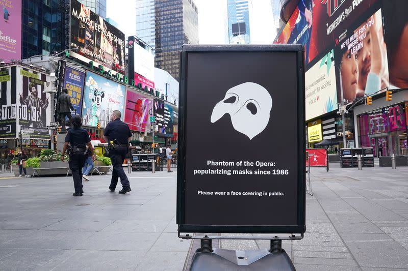 "A ""Phantom of the Opera"" sign asks people to wear a mask in public in the Manhattan borough of New York City"