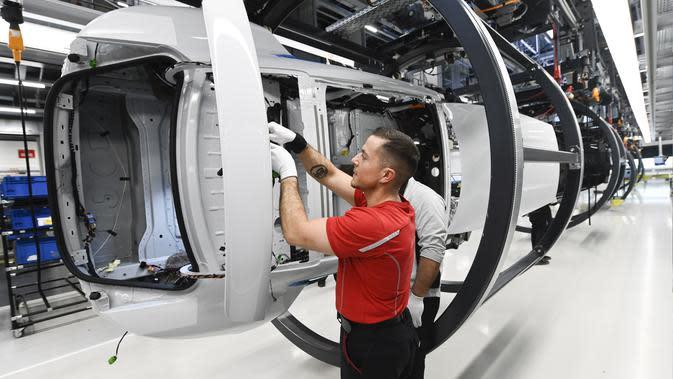 Mekanik melakukan pengecekan rangka mobil listrik. (AFP Photo/Thomas Kienzie)