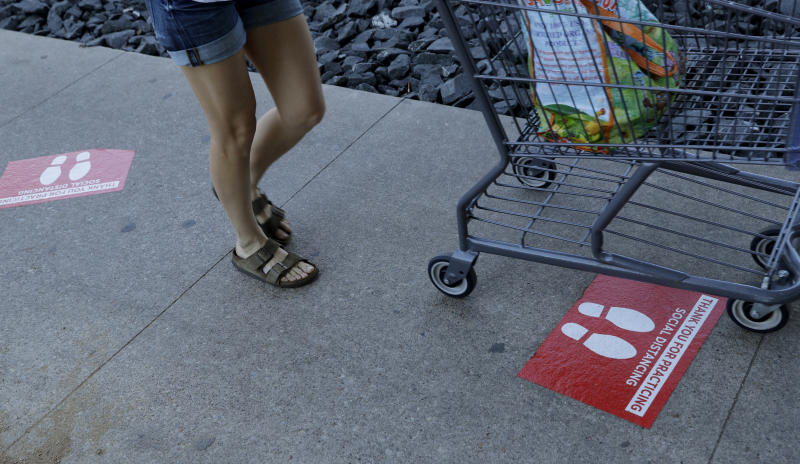 Signs that assist with social distancing are placed where shoppers wait in line at a grocery store in Austin, Texas, Wednesday, March 25, 2020. Austin is under Stay at Home orders to help battle the effects of COVID-19. (AP Photo/Eric Gay)