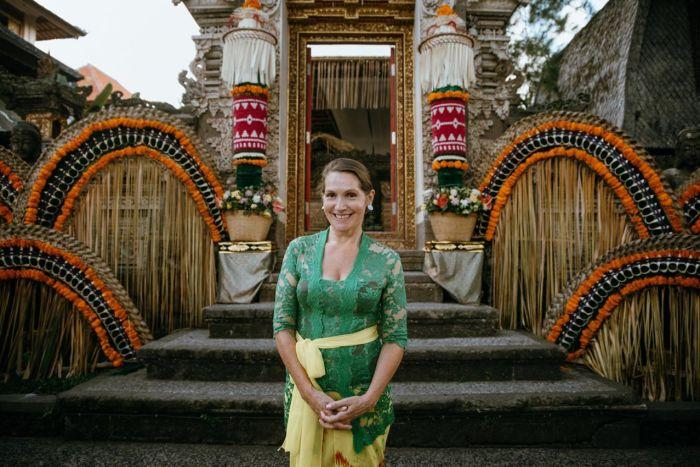 A woman standing outside a traditional building in Bali