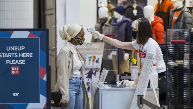 Asisten toko yang mengenakan masker memeriksa suhu tubuh seorang pelanggan di CF Toronto Eaton Center, Toronto, Kanada, 6 Oktober 2020. Jumlah kasus harian COVID-19 di Kanada terus bertambah. (Xinhua/Zou Zheng)