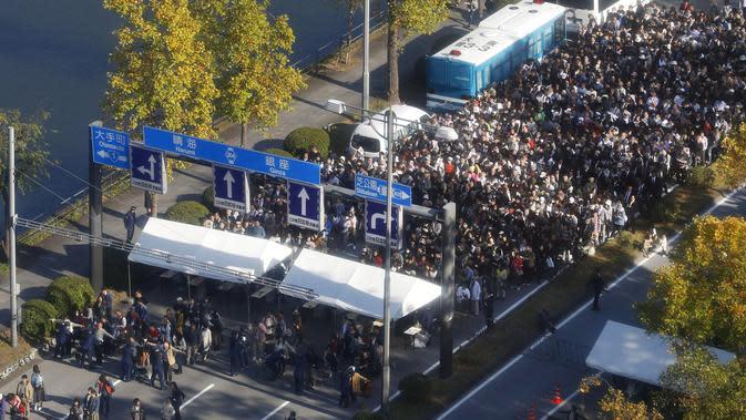 Ribuan warga berbaris untuk menerima pemeriksaan keamanan sebelum parade kerajaan Kaisar Jepang Naruhito dan Permaisuri Masako di Tokyo, Jepang, Minggu (10/11/2019). (Shinji Kita / Kyodo News via AP)