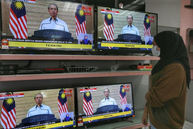 A woman watches a live broadcast of Prime Minister Tan Sri Muhyiddin Yassin on the recovery movement control order in Kuala Lumpur June 7, 2020. ― Picture by Ahmad Zamzahuri