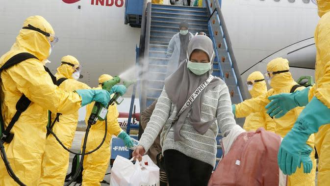 Petugas menyemprotkan cairan disinfektan ke WNI yang dievakuasi dari Wuhan, China saat tiba di bandara internasional Hang Nadim, Batam, Minggu (2/2/2020). Para WNI langsung ke luar pesawat untuk selanjutnya menuju Natuna, Kepulauan Riau. (Photo by Handout/Indonesian Embassy/AFP)
