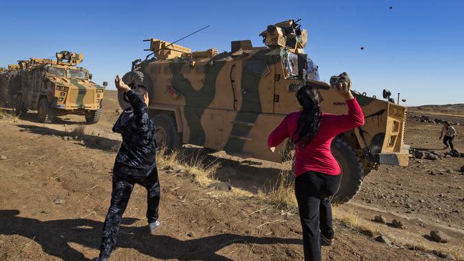 Dua wanita Kurdi melemparkan batu ke kendaraan militer Turki di dekat kota Al-Muabbadah, bagian timur laut Hassakah, Suriah (8/11/2019). Pelemparan batu terjadi saat militer Turki melakukan konvoi dengan militer Rusia. (AFP/Delil Souleiman)