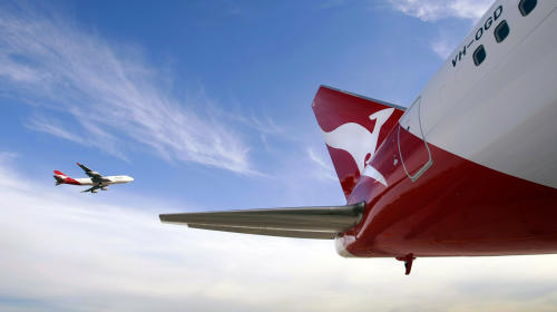 File picture shows a Qantas Boeing 747 flying past a 767 airplane with a newly unveiled Qantas logo on its tail in Sydney