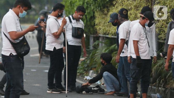 Polisi berpakaian kaus putih memeriksa seorang anak muda yang dicurigai terlibat kericuhan di kawasan Tugu Tani, Jakarta, Selasa (13/10/2020). Sejumlah pemuda diamankan polisi karena dicurigai terlibat kericuhan di kawasan Tugu Tani. (Liputan6.com/Helmi Fithriansyah)
