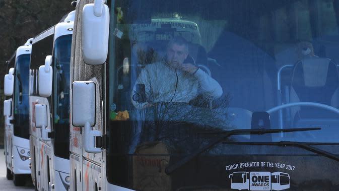 Bus menunggu warga yang dipulangkan dari Wuhan di Rumah Sakit Arrowe Park, Wirral, Inggris, Minggu (2/2/2020). Gelombang kedua warga Inggris yang dipulangkan dari Wuhan ini akan dikarantina bersama 83 orang lainnya. (Photo by Lindsey Parnaby/AFP)