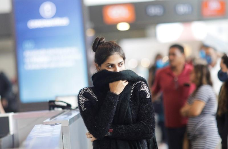 A passenger covers her face as she walks at Galeao international airport during the coronavirus disease (COVID-19) outbreak in Rio de Janeiro