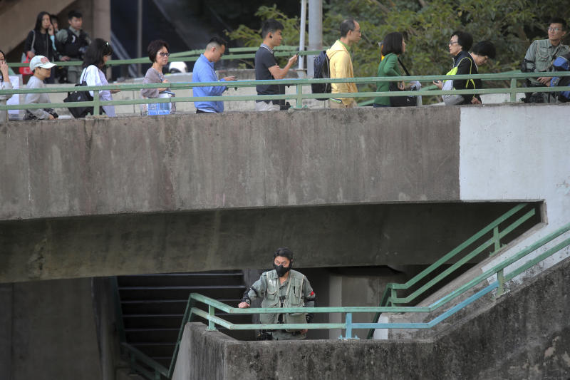 A riot policeman stands as voters line up outside of a polling place in Hong Kong, Sunday, Nov. 24, 2019. Voting was underway Sunday in Hong Kong elections that have become a barometer of public support for anti-government protests now in their sixth month. (AP Photo/Kin Cheung)