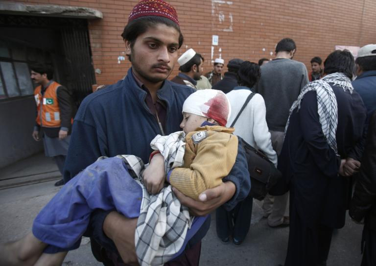 A man carries his brother who was injured in a grenade attack in Peshawar
