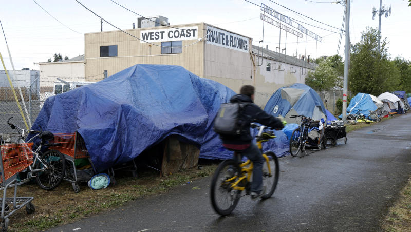 FILE - In this Sept. 19, 2017, file photo, a person cycles past tents set up along a pathway in Portland, Ore. A measure to tax the incomes of the wealthiest residents and the profits of the biggest businesses to raise $2.5 billion over a decade to address the homeless crisis sailed to victory in the Portland, Oregon metropolitan region even as the state faces crippling revenue losses and record-high unemployment. Nearly 60% of voters in the three counties that make up the greater Portland region approved the tax amid a greatest economic turmoil in years, a sign of just how intractable the homeless problem has become in the liberal Pacific Northwest city. (AP Photo/Ted S. Warren, File)