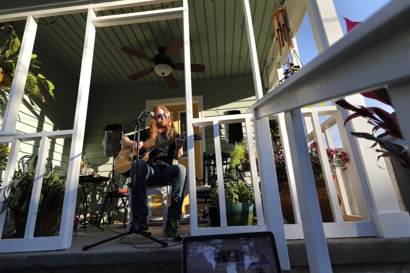Adam Pearce performs a concert from his front porch in Jefferson Parish, La., a suburb of New Orleans, Wednesday, April 29, 2020. With New Orleans music venues shuttered for more than a month now because of the coronavirus outbreak, musicians and fans are finding new places to connect – porches, living rooms, studios and lawns – and reaching their largest audiences online, many streaming performances live on social media platforms. But for the city's club owners awaiting the green light to reopen there's concern about all the uncertainties, like how long it may take tourists to return, how soon the music scene will rebound and when it does, what it will look like. (AP Photo/Gerald Herbert)