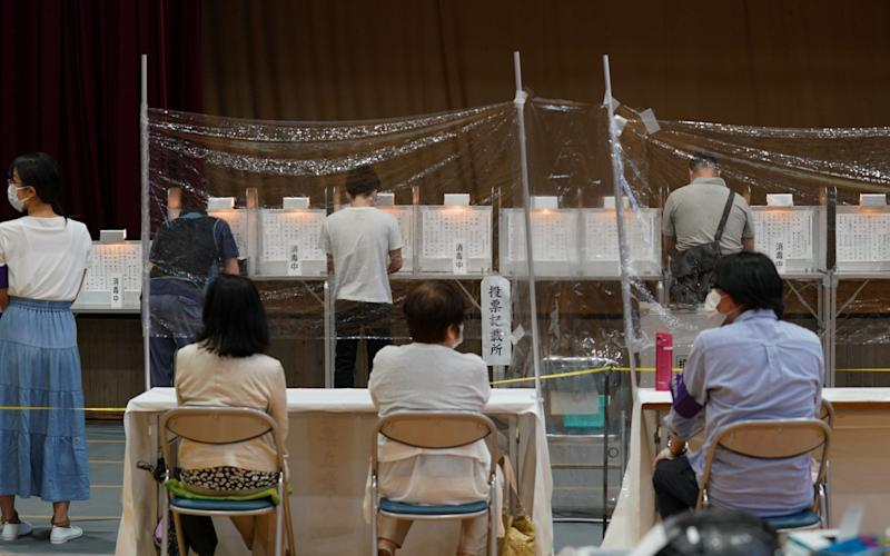Election officials observe from behind a vinyl screen at a polling station in Tokyo - KIMIMASA MAYAMA/EPA-EFE/Shutterstock