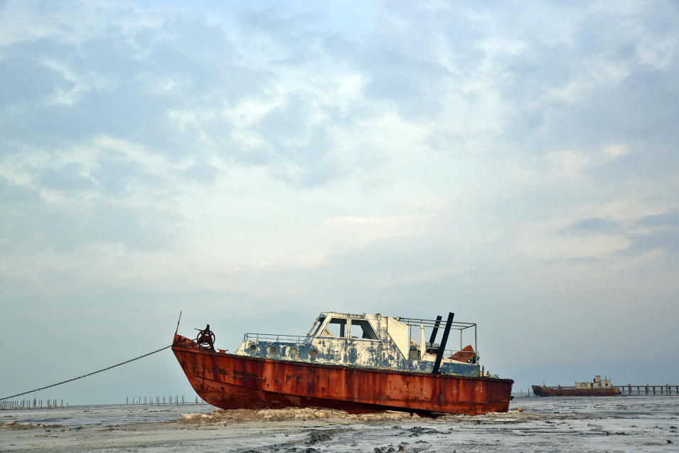 In this Sunday, Feb. 16, 2014 photo, an abandoned boat is stuck in the the solidified salts at Lake Oroumieh, northwestern Iran. Oroumieh, one of the biggest saltwater lakes on Earth, has shrunk more than 80 percent to 1,000 square kilometers (nearly 400 square miles) in the past decade, mainly because of climate change, expanded irrigation for surrounding farms and the damming of rivers that feed the body of water, experts say. (AP Photo/Ebrahim Noroozi)