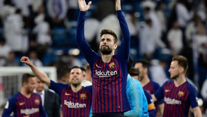 Bek Barcelona, Gerard Pique dan timnya berselebrasi setelah menang atas Real Madrid pada laga leg kedua semifinal Copa del Rey di Stadion Santiago Bernabeu, Rabu (27/2). Barcelona merebut tiket final Copa del Rey usai menang 3-0. (JAVIER SORIANO / AFP)