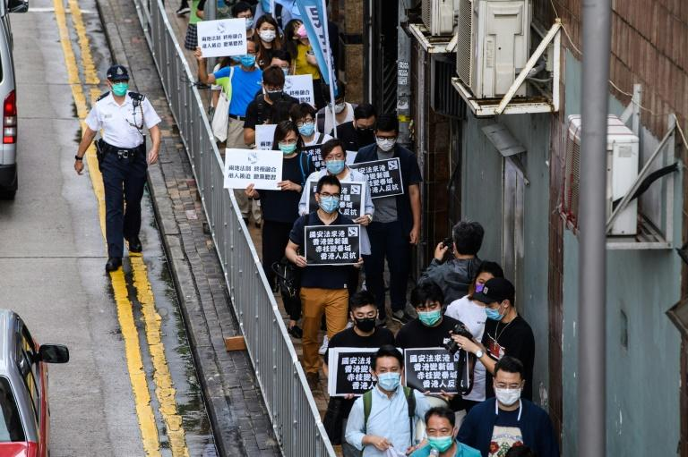 Pro-democracy protesters in Hong Kong hold black placards that warn that the city could turn into Xinjiang under a new Chinese law