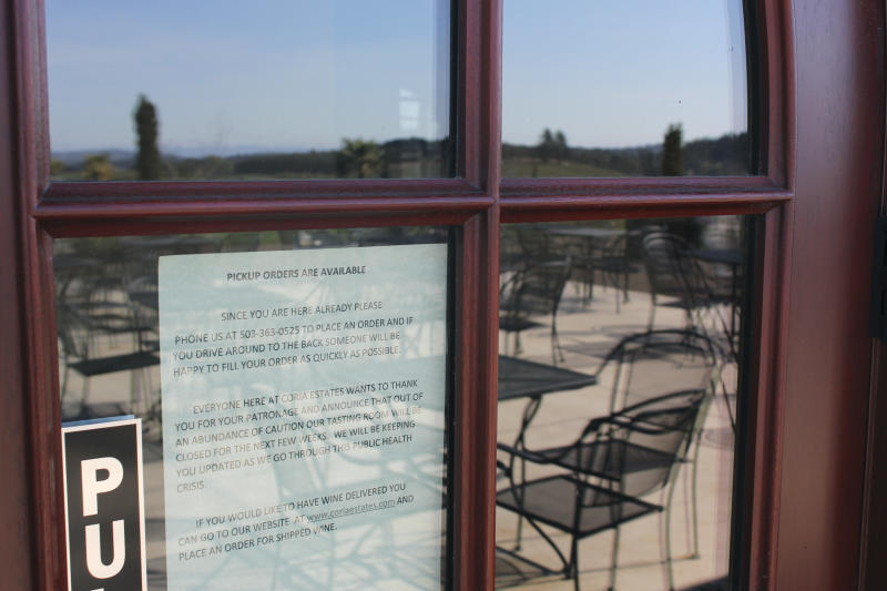 In this photo taken Tuesday, April 14, 2020, a sign announces that Coria Estates, a winery on the outskirts of Salem, Ore., is closed except for pickup, as the vacant patio is reflected. Oregon is in its fourth week of lockdown. Oregonians can't enter state parks in mountains and in valleys now blooming with springtime flowers, or go to the state's trademark wineries and microbreweries. But Oregon appears to be an outlier as coronavirus cases start to peak in each state. Of all the states in America, Oregon should have the fewest COVID-19 deaths per capita when the peak comes here, according to researchers at the University of Washington who developed a closely watched model. (AP Photo/Andrew Selsky)