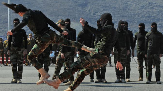 Pasukan perempuan Peshmerga bertarung melawan pria saat berlatihan dalam upacara kelulusan di Kota Soran, Irak, Rabu (12/2/2020). Latihan militer pasukan bersenjata Kurdi tersebut dilakukan sekitar 100 kilometer timur laut ibu kota otonomi wilayah Kurdi di Irak, Arbil. (SAFIN HAMED/AFP)