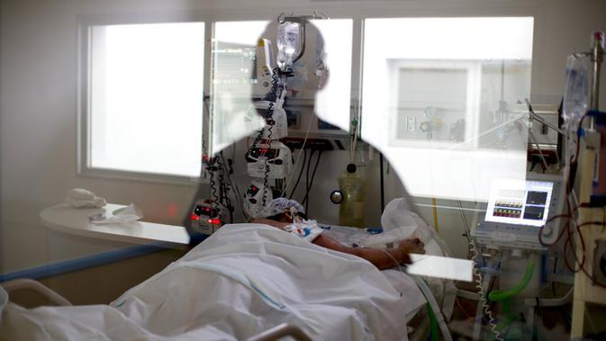 Seorang perawat tercermin pada jendela saat melihat pasien COVID-19 di Rumah Sakit El Cruce Dr. Nestor Carlos Kirchner, pinggiran Buenos Aires , Argentina, 15 September 2020. Kasus aktif COVID-19 Argantina terbanyak ketujuh di dunia, yaitu 129.641 kasus. (AP Photo/Natacha Pisarenko, File)