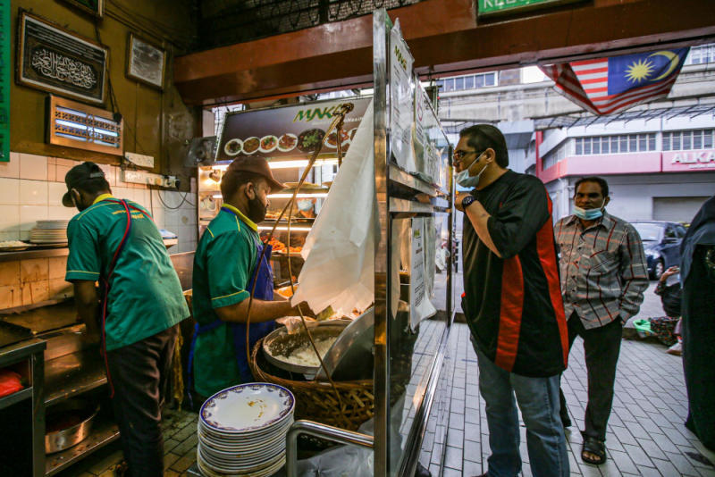 Customers queue up to buy food at Nasi Kandar Yaseem in Kuala Lumpur on the first day of the conditional movement control order May 4, 2020. — Picture by Hari Anggara