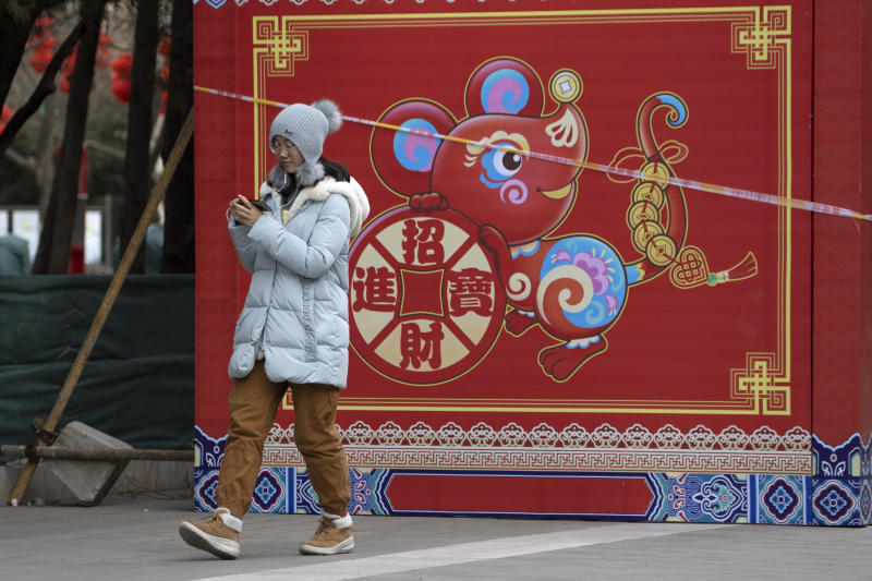 """A woman walks a depiction of a Rat with the words """"Bring in wealth and treasures"""" ahead of the Chinese Lunar New Year Year of the Rat celebrations in Beijing on Thursday, Jan. 16, 2020. China's government welcomed an interim trade deal with Washington and said Thursday the two sides need to address each other's """"core concerns."""" (AP Photo/Ng Han Guan)"""