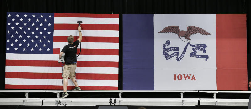 FILE - In this Sept. 14, 2015, file photo, a worker steams wrinkles out of a US flag before the arrival of President Barack Obama at a town hall meeting, at North High School in Des Moines, Iowa. Few states have changed politically with the head-snapping speed of Iowa. (AP Photo/Charlie Neibergall, File)