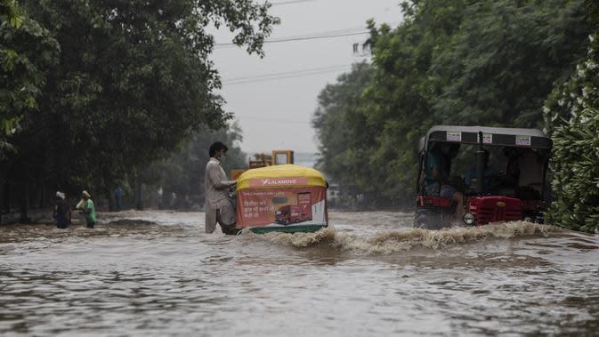 Sebuah kendaraan melintasi jalan yang tergenang air setelah hujan monsun di Gurgaon di pinggiran New Delhi (19/8/2020). Jumlah korban dari banjir tahunan di seluruh Asia Selatan naik menjadi hampir 1.300. (AFP/Xavier Galiana)