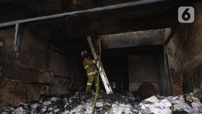 Petugas pemadam kebakaran melakukan pembasahan bioskop Grand Theater yang terbakar di Simpang Lima Senen, Jakarta, Jumat (9/10/2020). Unjuk rasa menentang disahkannya Omnibus Law UU Cipta Kerja berujung aksi anarkis merusak berbagai fasilitas umum pada Kamis malam (8/10). (merdeka.com/Dwi Narwoko)
