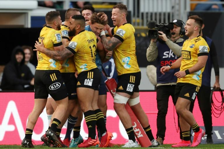 The Hurricanes' players celebrate a Dane Coles try as their former teammate and Blues debutant Beauden Barrett is dragged in for some good-natured ribbing and hair ruffling