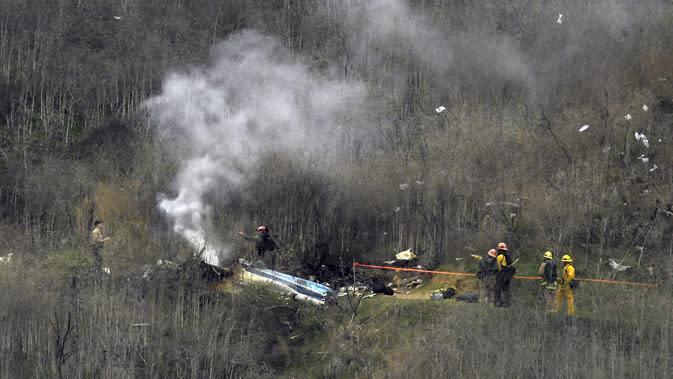 Petugas pemadam kebakaran berusaha memadamkan api di lokasi kecelakaan helikopter yang ditumpangi pebasket NBA Kobe Bryant di Calabasas, California (26/1/2020). Putri Bryant yang berusia 13 tahun, Gianna Bryant juga ikut meninggal dunia dalam insiden tersebut. (AP Photo/Mark J. Terrill)