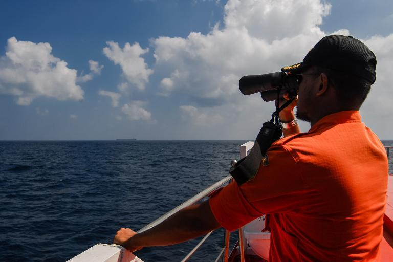 Indonesian National Search and Rescue Agency personnel scan the seas in the Malacca Strait off Aceh province on March 12, 2014 during the continued search for the missing Malaysia Airlines flight MH370
