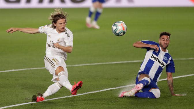 Gelandang Real Madrid, Luka Modric melepaskan tembakan yang berusaha dihentikan pemain Alaves, Victor Camarasa pada lanjutan Liga Spanyol di stadion Alfredo di Stefano, Sabtu (11/7/2020). Real Madrid menang 2-0 lewat gol Karim Benzema dan Marco Asensio. (AP Photo/Bernat Armangue)