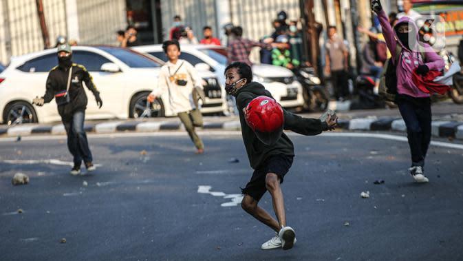 Massa melemparkan batu ke arah polisi saat bentrok di kawasan Pejompongan, Jakarta, Rabu (7/10/2020). Belum bisa dipastikan apakah aksi tersebut berkaitan dengan isu aksi penolakan pengesahan UU Omnibus Law Cipta Kerja. (Liputan6.com/Faizal Fanani)