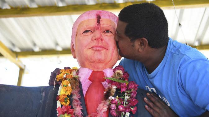 Bussa Krishna (33) mencium patung Presiden AS Donald Trump saat memanjatkan doa di Desa Konney, Telangana, negara bagian India selatan (14/2/2020). Trump dan istrinya Melania juga akan berkunjung ke rumah Perdana Menteri Narendra Modi, pada 24 Februari. (AFP/Noah Seelam)