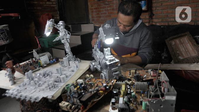 Perajin menyelesaikan pembuatan lampu duduk dari limbah komputer di kawasan Griya Asri Pamulang, Tangerang Selatan, Senin (31/08/2020). Beragam produk seperti lampu duduk, boneka robot, asbak dari limbah komputer dipasarkan dengan harga Rp 250ribu - Rp 350ribu per item. (merdeka.com/Arie Basuki)