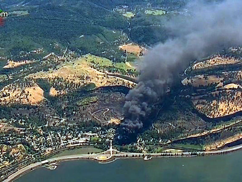 FILE - In this June 3, 2016, file image from video provided by KGW-TV, smoke billows from a Union Pacific train that derailed near Mosier, Ore., in the Columbia River Gorge. The Trump administration on Monday, May 11, 2020, moved to block a Washington state law that imposed safety restrictions on oil shipments by rail in response to numerous explosive accidents. The Department of Transportation determined federal law preempts the state's mandate that crude from the oil fields of the Northern Plains have more of its volatile gases removed prior to being loaded onto rail cars. (KGW-TV via AP, File)