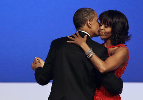 FILE - This Jan. 21, 2013 file photo shows President Barack Obama kissing first lady Michelle Obama during their dance at the Commander-in-Chief Inaugural Ball at the Washington Convention Center in Washington. Nobody would call bangs a new trend, but when the first lady's involved, things take on more significance. In fact, President Barack Obama did call his wife Michelle's new hairdo the most significant event of his second inauguration. (AP Photo/Jacquelyn Martin, File)