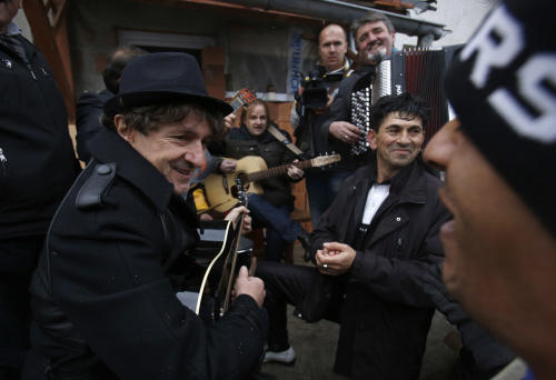 Bosnia's most popular former rock star, now composer of ethnic music inspired by Roma culture, Goran Bregovic, left, plays guitar surrounded by Bosnian Roma people in Sarajevo, on Tuesday, Dec. 10, 2013. Bosnia's most popular musician is searching for talented Roma children to help them get an education in music. On Tuesday, 63-year-old former rock star Goran Bregovic visited Sarajevo's biggest Roma settlement of Gorica. That's the same name he has given his new foundation, which will provide scholarships to Roma kids who wish to study music but can't afford to. (AP Photo/Amel Emric)