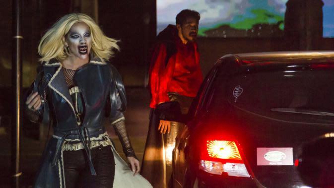 Seorang aktor berpakaian vampir tampil di taman hiburan horor Hopi Hari, pinggiran Vinhedo, Sao Paulo, Brasil, Jumat (4/9/2020). Karena pembatasan akibat COVID-19, taman hiburan horor Hopi Hari menampilkan pertunjukan secara drive-thru. (AP Photo/Carla Carniel)